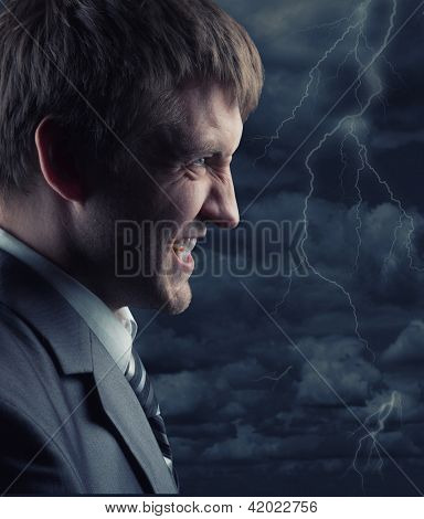 Angry businessman against storm at night