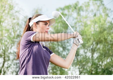 Woman playing golf, standing in pose after hit