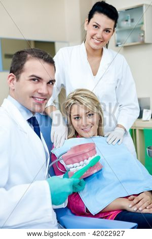 Dentist teaching a female patient how to brush teeth