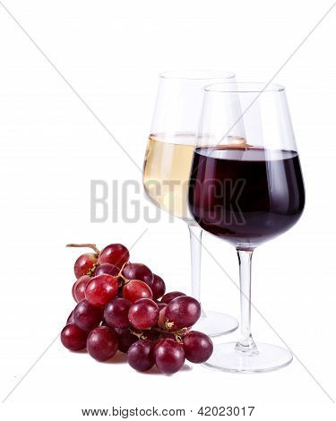 Two Wine Glasses With Red And White Wine And Grapes