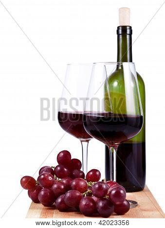 Two Wine Glasses With Red Wine, Bottle Of Wine And Grapes