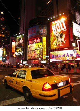 Taxi Cab Driving Through Times Square At Night