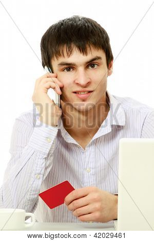 A young man with a credit card in front of a laptop, talking on the phone, isolated on white
