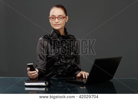 Businesswoman in black fancy shirt, red glasses, texting on mobile phone, using laptop computer.