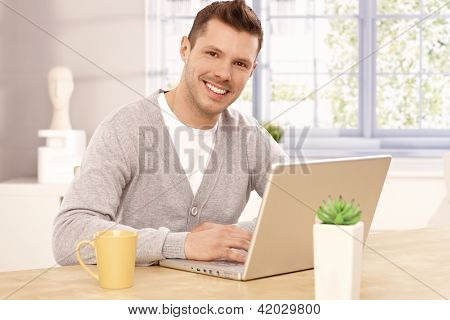 Handsome young man browsing internet at home, smiling, looking at camera.