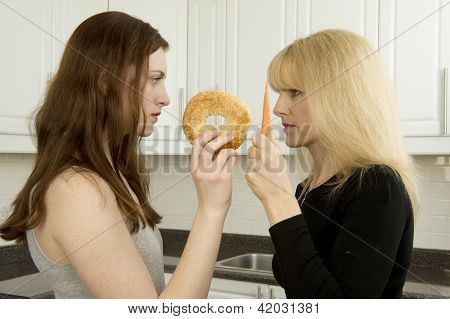 Young Woman And Mother Argue In The Kitchen Over High Glycemic Index  Bagel Or  Low Glycemic Index