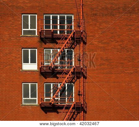 Red brick building with three rows of windowed fire escapes