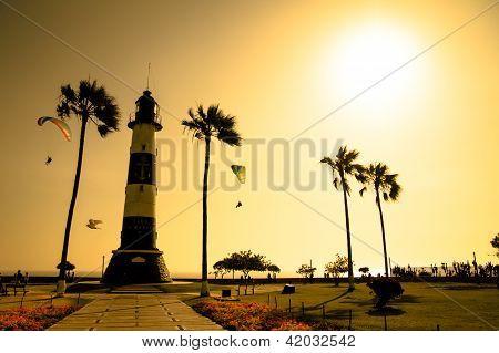 Lighthouse silhouette among golden sunset sea