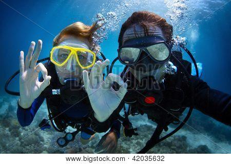 Debaixo d'água disparar de um jovem casal, mergulho com scuba em um mar tropical e mostrando sinal ok