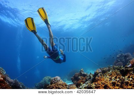 Underwater shoot of a young lady snorkeling and diving on a breath hold over vivid coral reef of tropical island