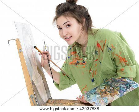 attractive teen girl painter drawing portrait with oil paints, professional painter at work over white background