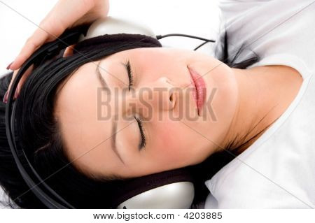 Top View Of Laying Female Enjoying Music On An Isolated Background