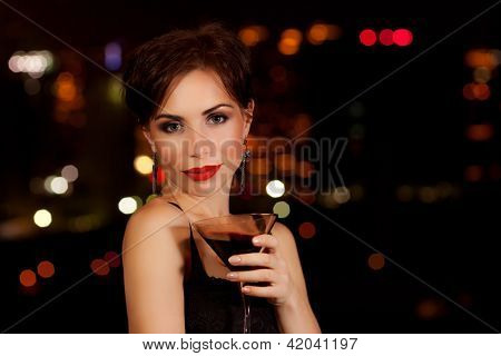Photo of a beautiful woman having martini in outdoor restaurant, celebration party, city nightlife lifestyle, glamorous lady with drink, female enjoying cocktail