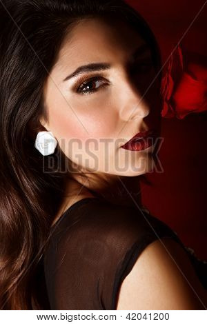 Photo of beautiful brunette woman with red rose isolated on dark background, closeup portrait of gorgeous female with perfect makeup, luxury beauty salon, Valentine day, passion and elegance concept