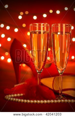 Photo of beautiful red romantic still life, two glass of champagne, shoes on high heels, luxury white pearl beads, fluffy feather, festive lights, holiday presents, Valentine day, love concept