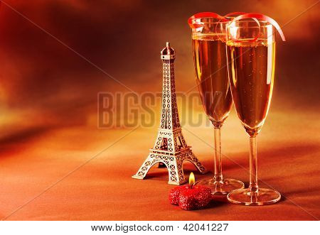 Photo of two wine glass decorated with red ribbon, heart-shaped candle and small Eiffel tower, beverage still life, Valentine day in Paris, dark grange background, love and romance concept