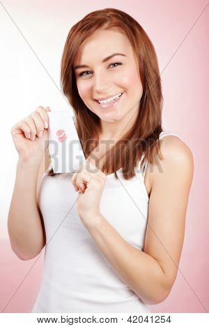 Picture of pretty woman holding in hands love letter with red lips print, closeup portrait of cheerful girl with postcard for Valentine day isolated on pink background, romantic relationship concept