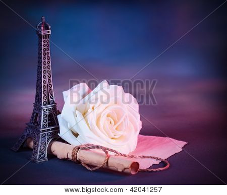 Image of festive greeting card with fresh white rose on the table decorated with small Eiffel tower, vintage photo, wedding in Paris, love letter on parchment, Valentine day in Europe
