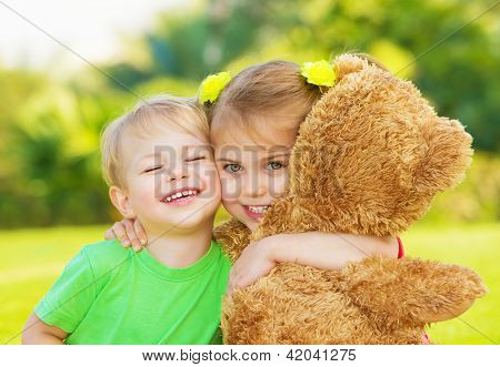 Photo two cute child hugging outdoors, brother and sister having fun on backyard in spring, nice little girl with adorable boy playing with big soft bear toy, best friends, happy childhood concept