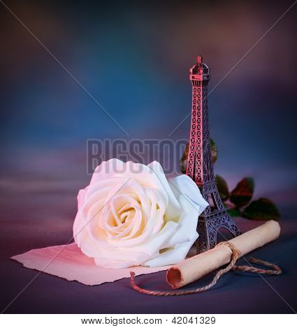 Picture of beautiful retro style still life over blue grunge background, white fresh rose flower, small decorative Eiffel tower, love letter, aged paper scroll with handwriting poem, Valentine day
