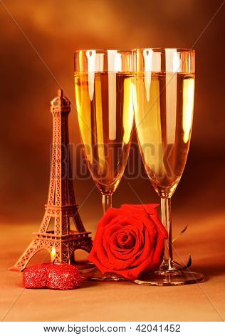 Image of festive romantic still life, alcoholic beverage, two glass with sparkling wine, honeymoon in Paris, travel to France, red fresh rose and heart-shaped candle, Valentine day, love concept