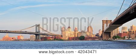 Manhattan Bridge and Brooklyn Bridge panorama over East River viewed from New York City Lower Manhattan waterfront at sunset.