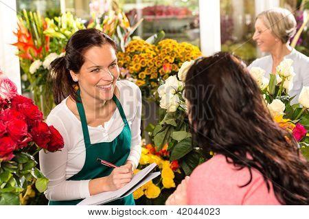 Florista feliz escrevendo falando mulher cliente de loja de flores