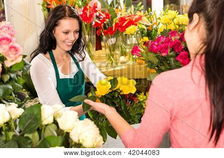 Cheerful flower shop florist customer buying yellow bouquet women