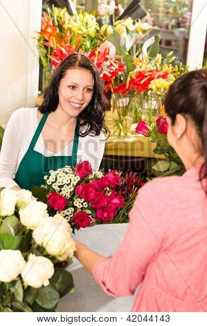Happy florist making roses bouquet women customer buying flower shop