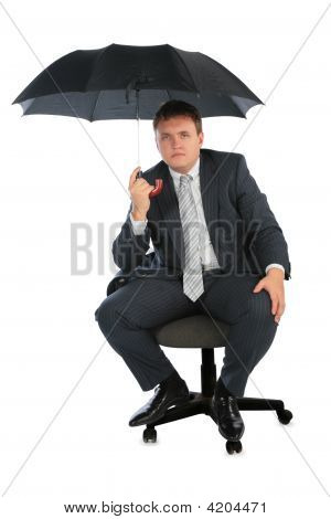 Businessman On Chair With Umbrella