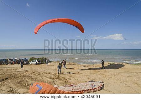 Para-gliders met on the beach.