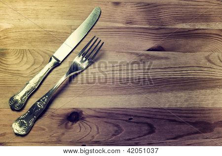 Old silver cutlery on wooden background, vintage image
