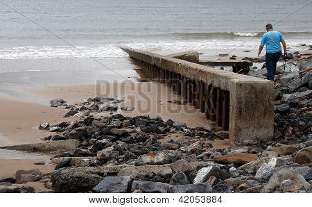 Man Walking On A Rugged Beach