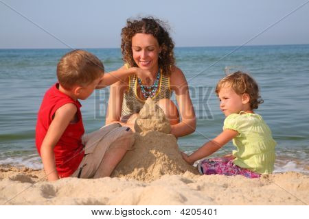 Mother With Children Playing With Sand On Beach