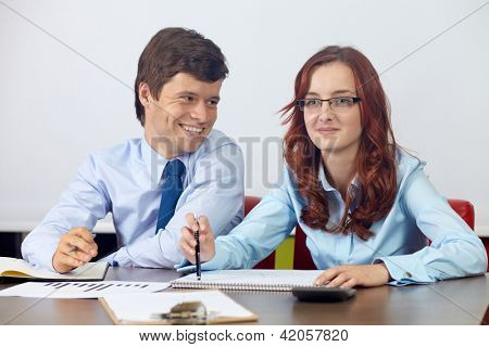 Young attractive businesswoman and businessman sitting together and talking about documents