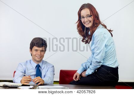 Young attractive happy businesswoman and businessman sitting together and talking about documents