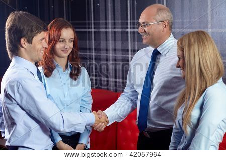Happy successful young businessman shaking hand with senior businessman,office in the background