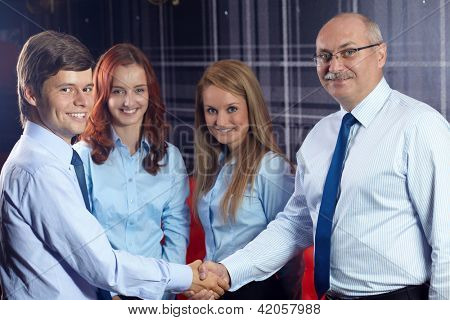 Happy successful young businessman shaking hand with senior businessman, office in the background
