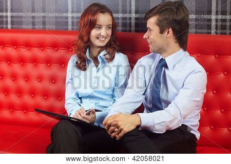 Young attractive happy smiling businesswoman and businessman sitting together and talking
