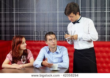 Young attractive couple sitting in restaurant and talking to handsome waiter