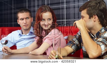 Young jealous angry man looking at his girlfriend sitting in a restaurant