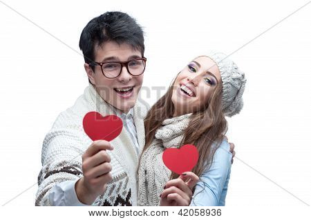 young cheerful casual couple holding red hearts