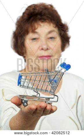 Elderly woman holds toy cart on her palm, shallow dof