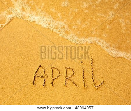 April - written in sand on beach texture - soft wave of the sea (months year series)