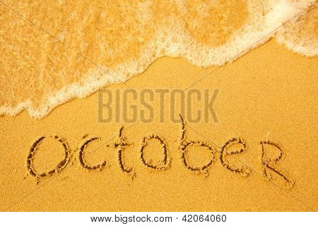 October - written in sand on beach texture - soft wave of the sea (months year series)
