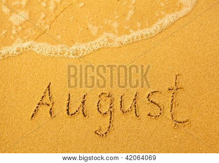 August - written in sand on beach texture - soft wave of the sea (months year series)