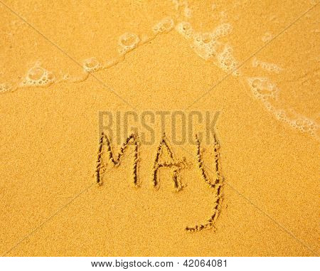 May - written in sand on beach texture - soft wave of the sea (months year series)