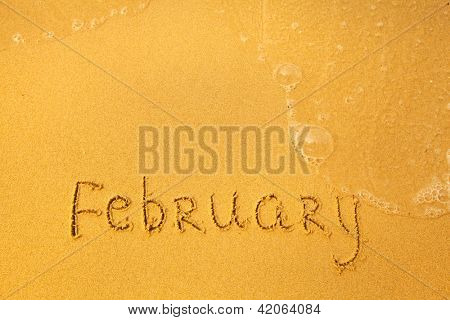 February - written in sand on beach texture - soft wave of the sea (months year series)