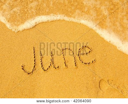 June - written in sand on beach texture - soft wave of the sea (months year series)
