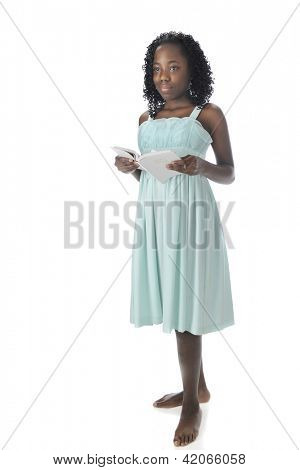 A beautiful African American tween looking up from reading the white Bible that's in her hands.  On a white background.